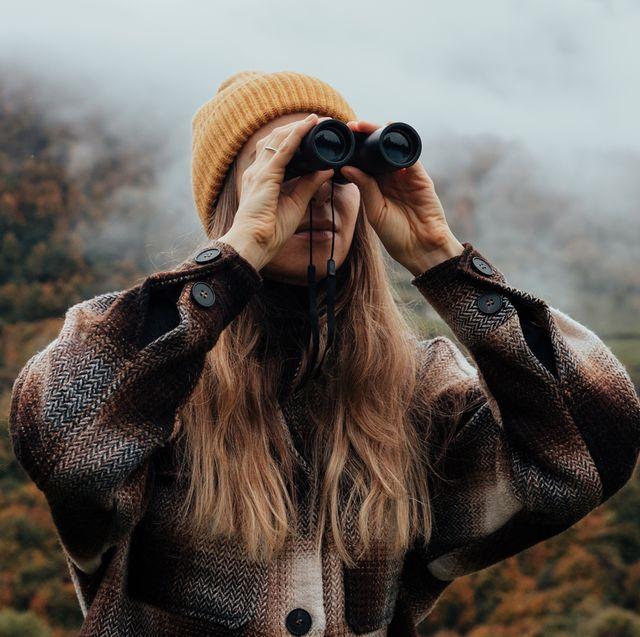 woman using binoculars in mountains