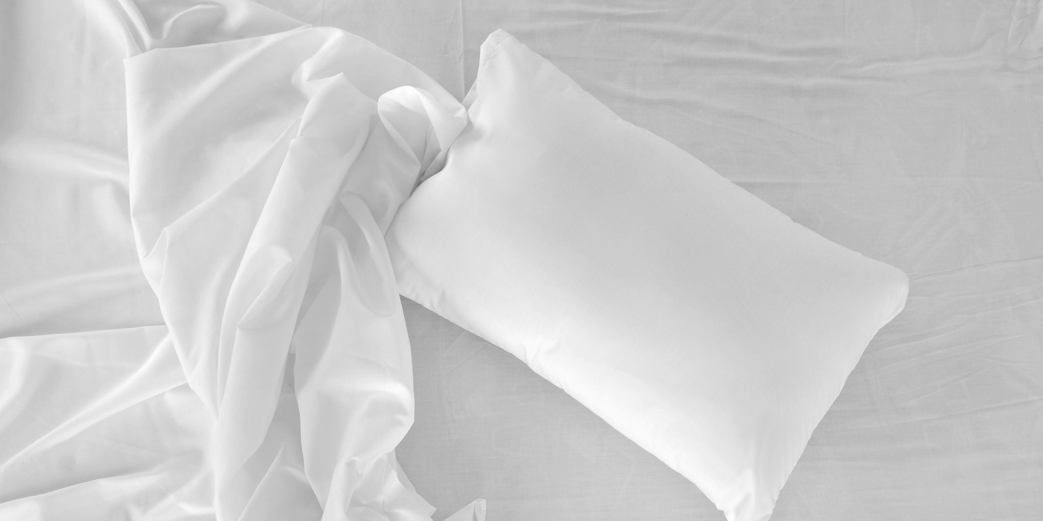 Bird's eye view of a white, unmade bed