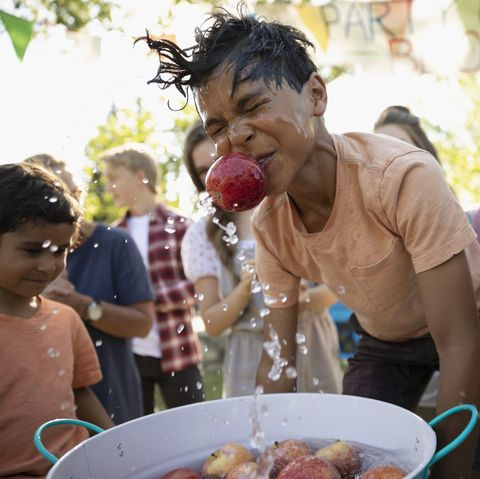 Playful boy splashing, bobbing for apples at summer neighborhood block party in park