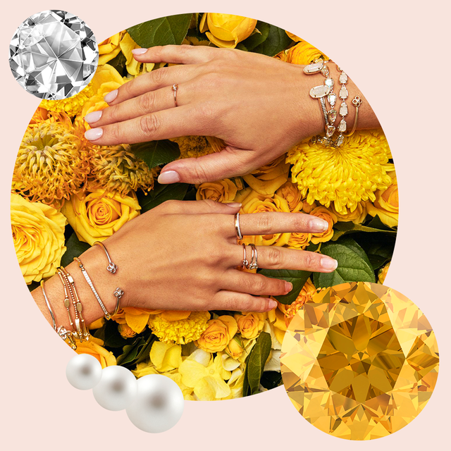 two womens hands with birthstone gem bracelets and rings displayed against yellow flowers