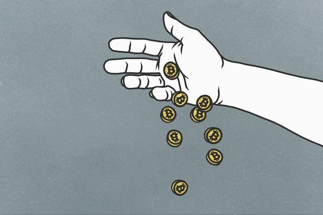 una mano dejando caer un puñado de monedas que representan tokens de bitcoin