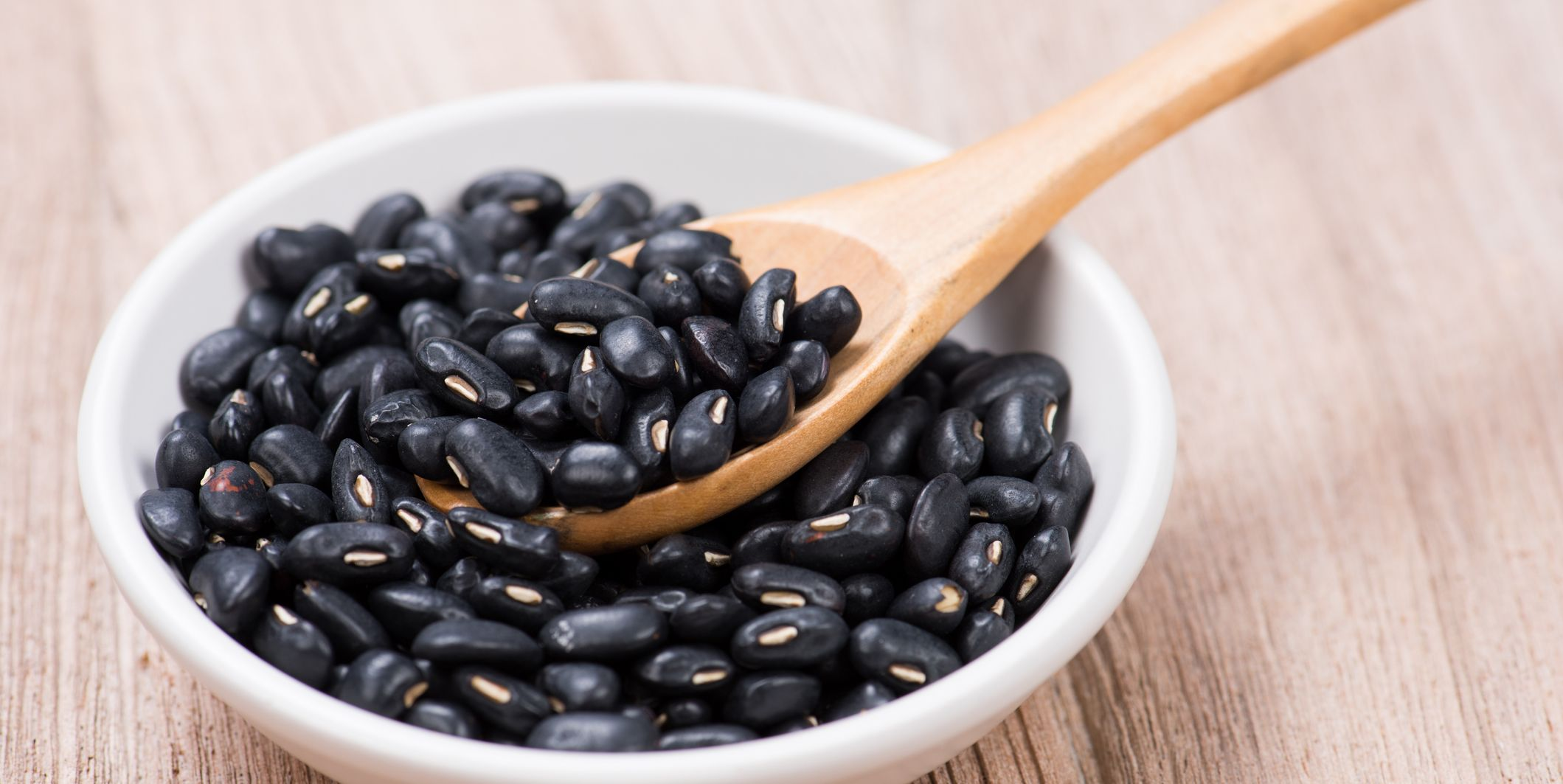 Black Beans in wooden spoon with seramic bowl