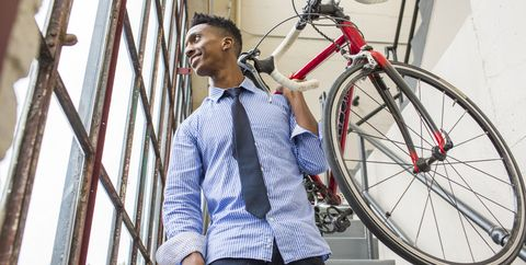 Black businessman descending staircase carrying bicycle