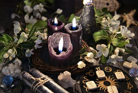 Black candles with runes, zodiac circle and spring flowers