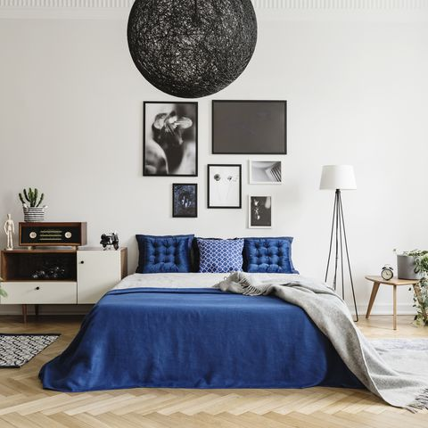 black chandelier in navy blue bedroom in tenement house floor lamp between king size bed and small table with pot and clock on it real photo concept