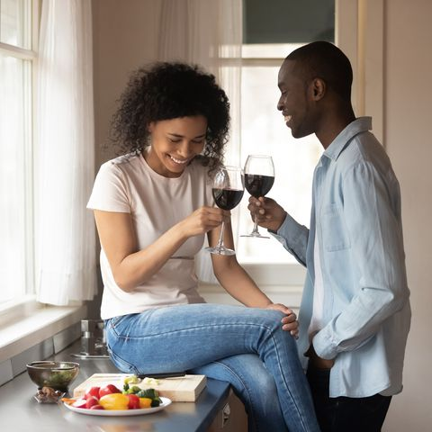 black couple enjoy romantic date with wine in the kitchen
