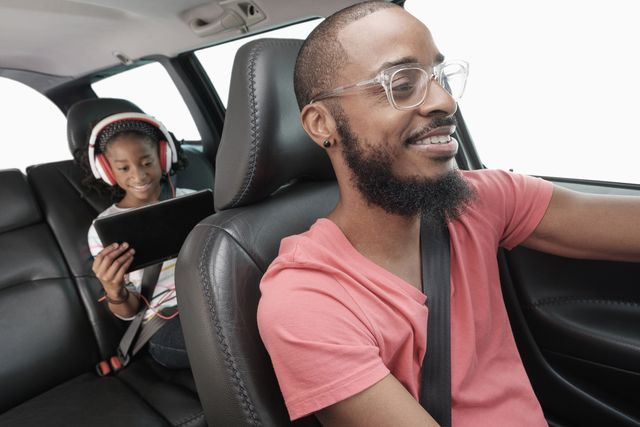 black father and daughter driving in car