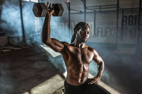 Black male athlete exercising with dumbbell in lunge position at gym.