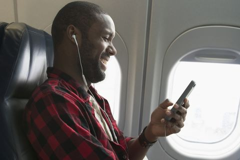 Black man listening to earbuds on airplane