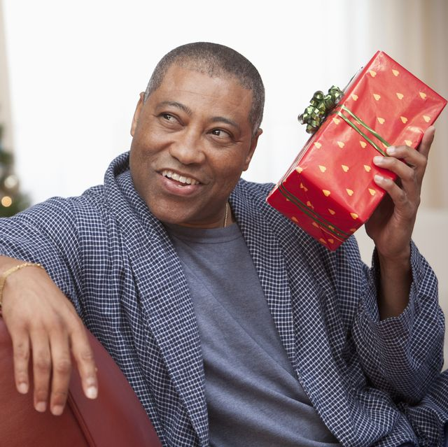 black man shaking gift in living room at christmastime