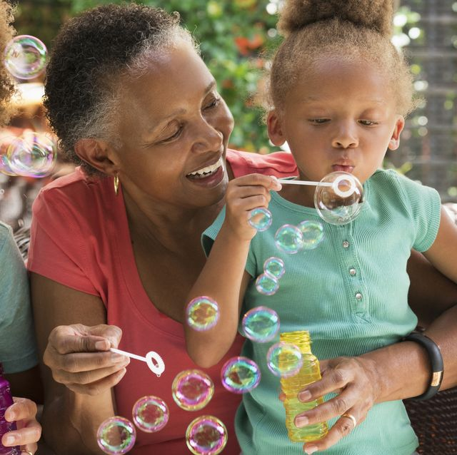 black multi generation family blowing bubbles outdoors