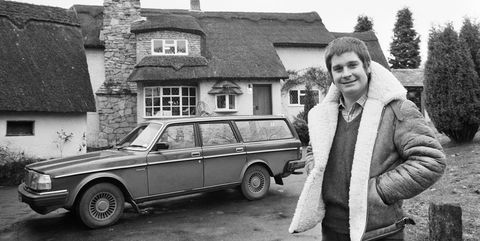 Black Sabbath singer Ozzy Osbourne pictured outside his new house, beside his Volvo car.