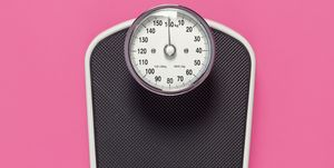 Black weighing scales on pink background