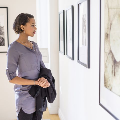 staycation ideas - Black woman admiring paintings in art gallery