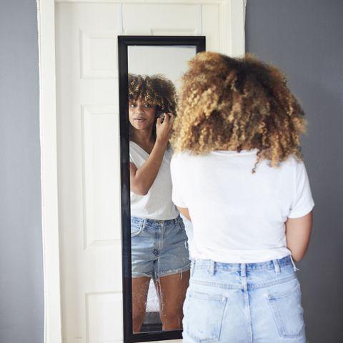 امرأة سوداء فحص الشعر في المرآة