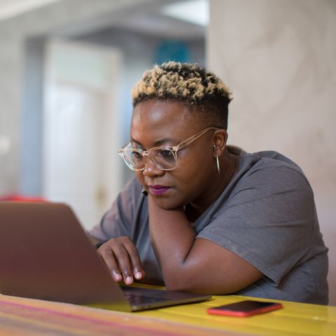 healthy dining out - Black woman looking closely at laptop