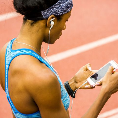 Black woman on track listening to cell phone with earbuds