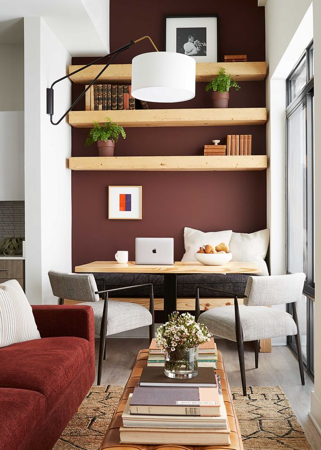 red walls, breakfast nook, wood table, cream chairs, orange couch designed by byron risdon
