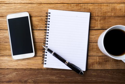 blank white diary with pen, coffee and smart phone