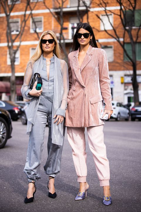 milan, italy   february 21 teresa andres gonzalvo and marta lozano, wearing a grey top, grey pants, black heels and zebra print bag l, and pink velvet blazer, pink pants and lilac heels r, are seen outside emporio armani show, during milan fashion week fallwinter 2020 2021 on february 21, 2020 in milan, italy photo by claudio laveniagetty images