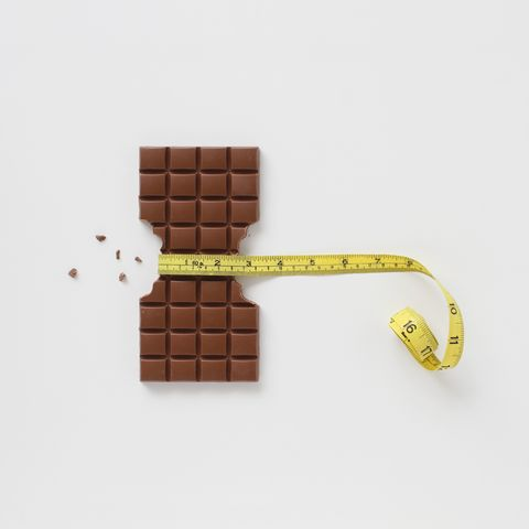 Block of chocolate bar with sides bitten off and chocolate crumbs with a tape measure around the middle
