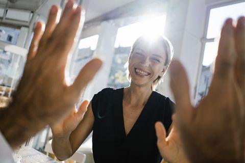 blond businesswoman high fiving a colleague