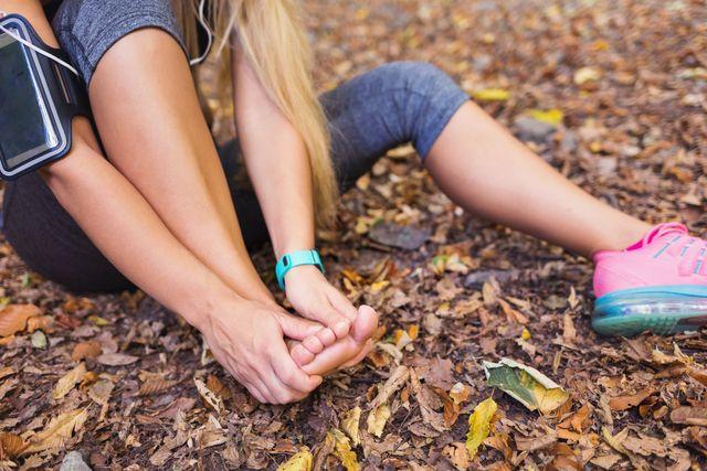 blond woman massaging her sprained foot