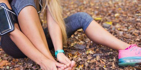 Blond woman massaging her sprained foot.
