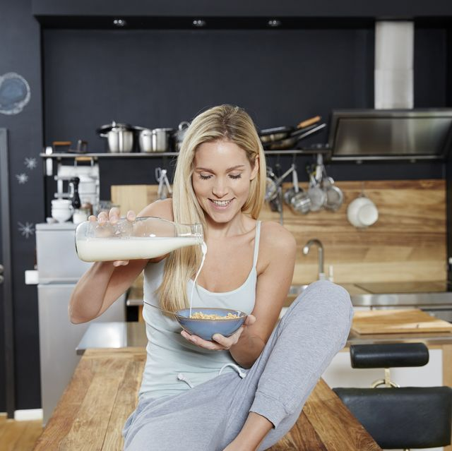 Blond woman sitting on kitchen table pouring milk on cereals