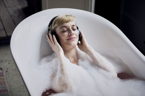 blond woman taking bubble bath in a loft listenung music with headphones