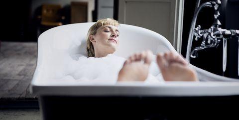 Blond woman taking bubble bath in a loft