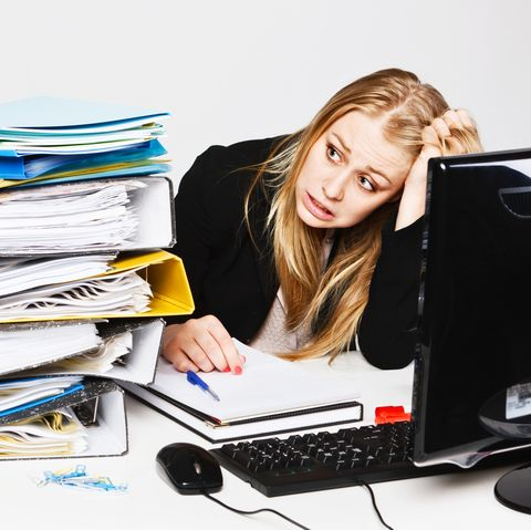 Blonde businesswoman tears hair out in frustration at workload