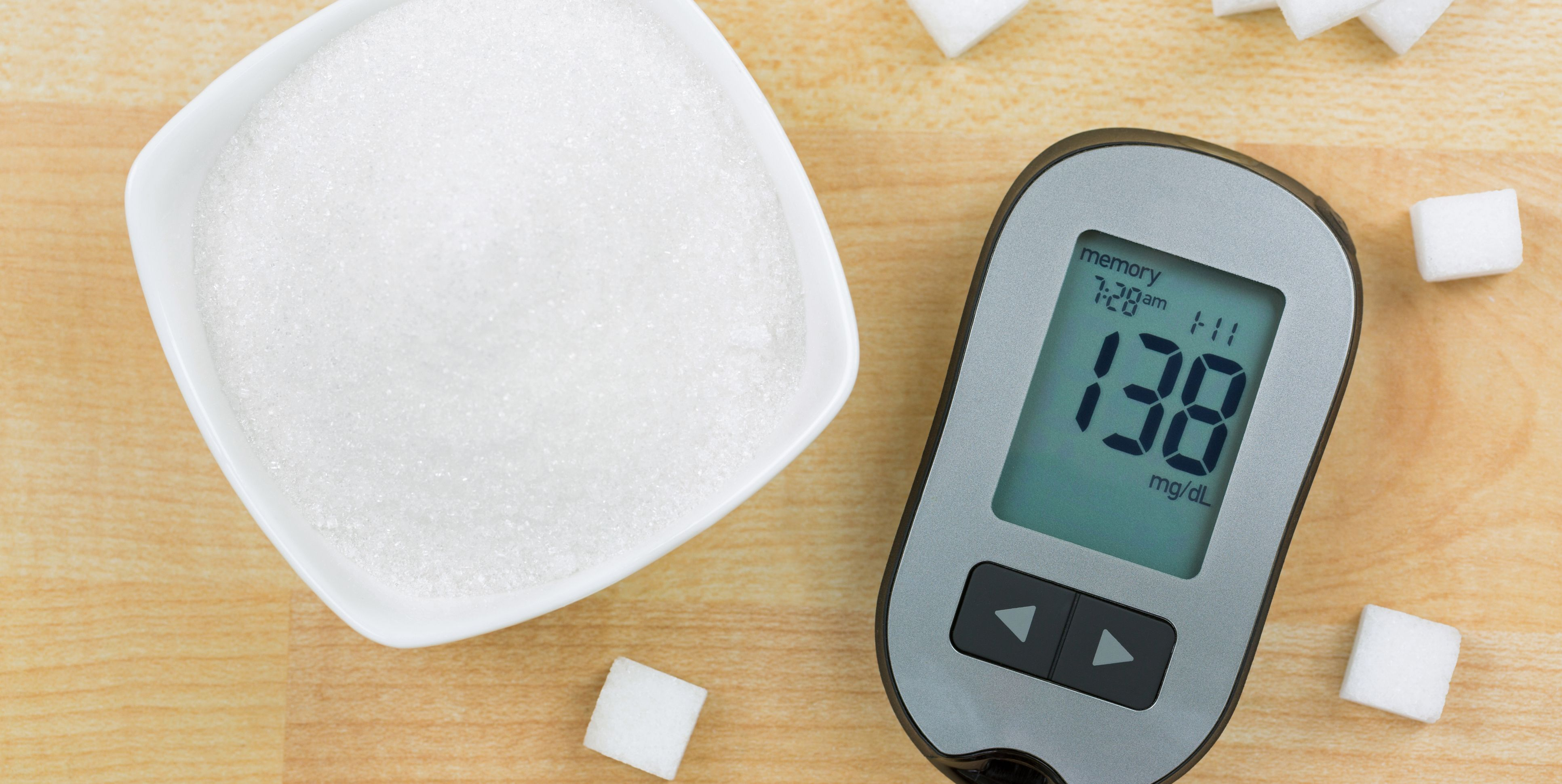 Blood Glucose meter device showing high blood sugar levels, next to sugar cubes