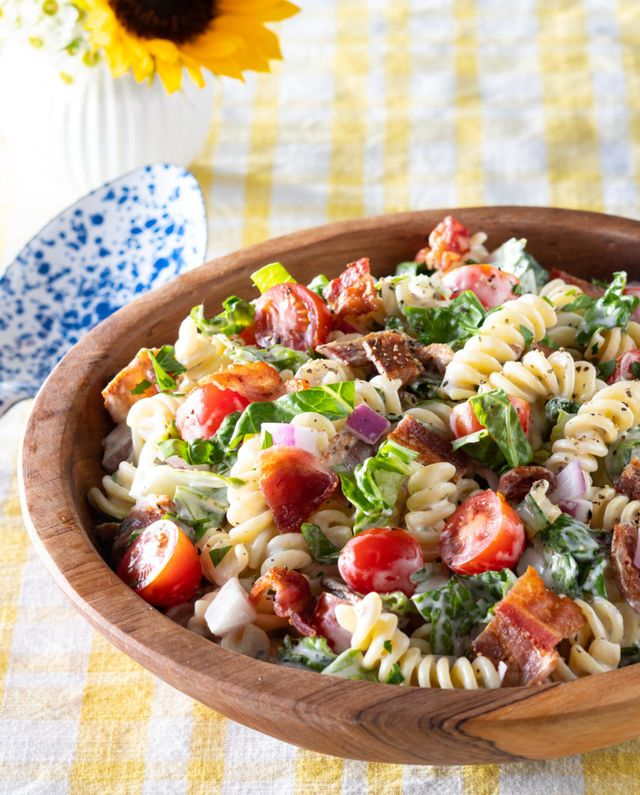 blt pasta salad in wood bowl on yellow linen