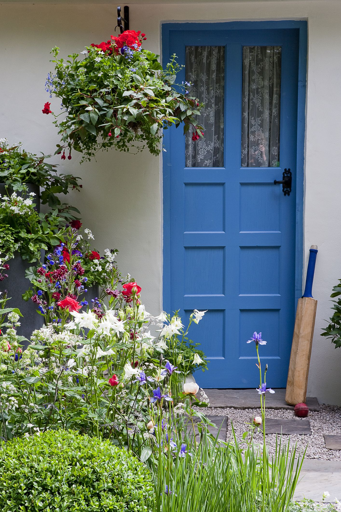 Blue Front Door With Cricket Bat And Planters