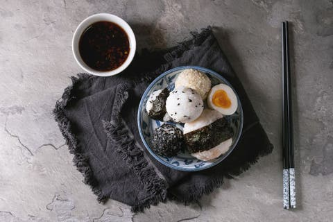 Blue plate with different size rice balls with black sesame and seaweed nori, served with soft boiled eggs, soy sauce, chopsticks over gray table. Asian style dinner. Top view with space