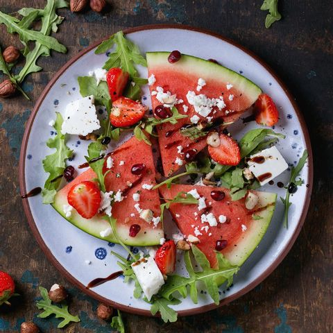 Blue spotted plate with watermelon and strawberry fruit salad with feta cheese, arugula, nuts and balsamic sauce, served over old dark wood background. Top view. Healthy eating concept. Square image