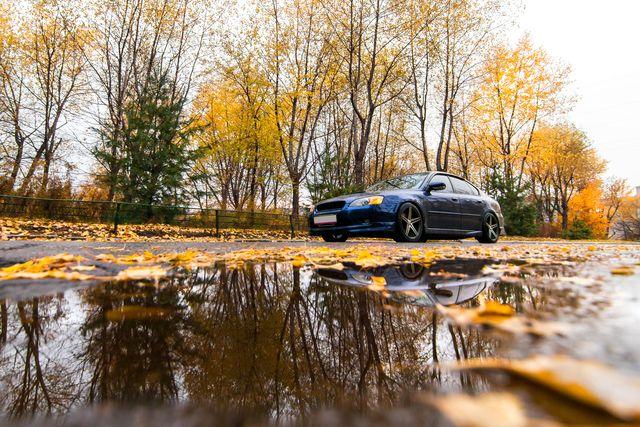 blue subaru legacy on autumn road in rainy day