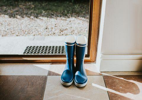 Bottes bleu welly assis par une porte arrière ouverte