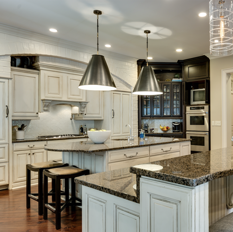 kitchen with two big black cone lights over the granite counter island