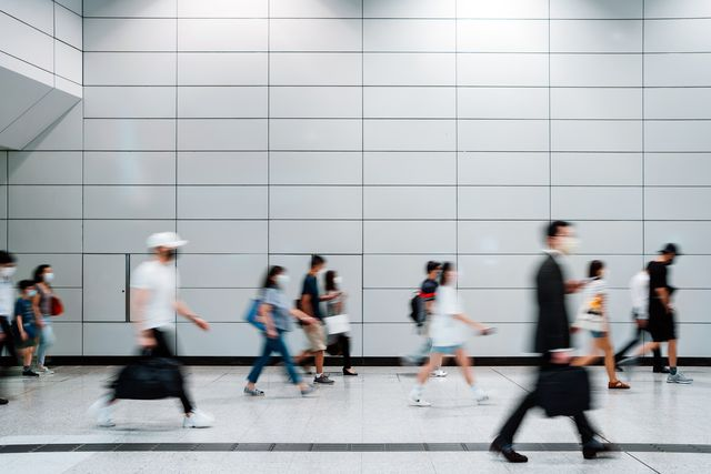 blurred motion of a crowd of busy commuters with protective face mask walking through platforms at subway station during office peak hours in the city
