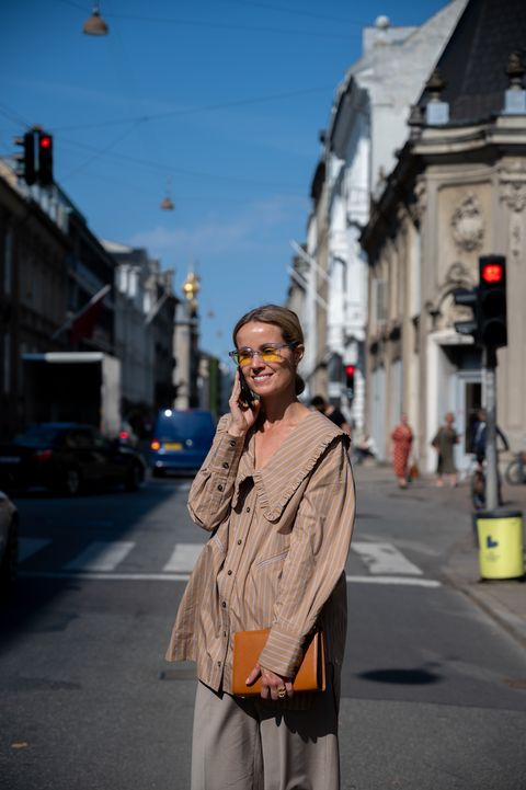 mujer con blusa cuello bobo beige a rayas, street style de copenhagen
