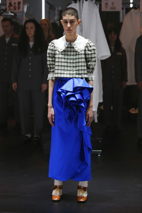 desfile de gucci, modelo con blusa de cuadros y cuello bobo y falda midi azul
