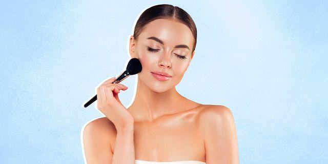 beautiful young woman applying foundation powder