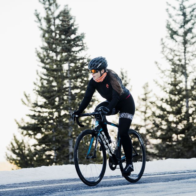 a young female cyclist riding her road bike in the winter on a snowy road