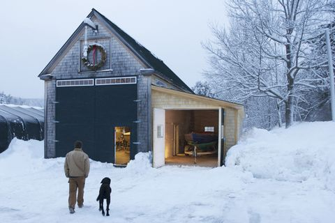 A boat builder,  with his dog at his side, walk through the snowy yard after a long winters day in the boat shed.