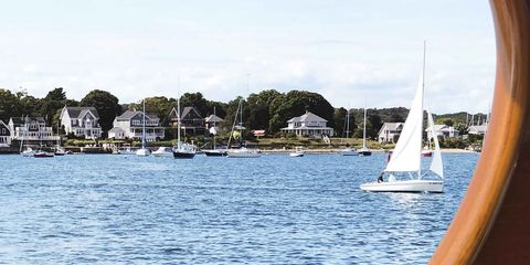 a view of the rhode island coastline from a boat there are sailboats in the water and houses lining the coast