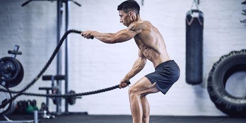 Gespierde man zonder shirt traint met battle ropes in de sportschool om vet kwijt te raken en spieren op te bouwen.