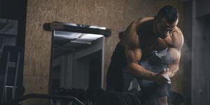 Bodybuilder chalking hands for deadlifts in gym