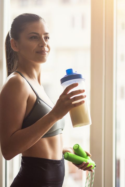 bodybuilder girl relax after exhausting training, young athlete drinking sports drink after workout, beautiful woman resting after exercising training
